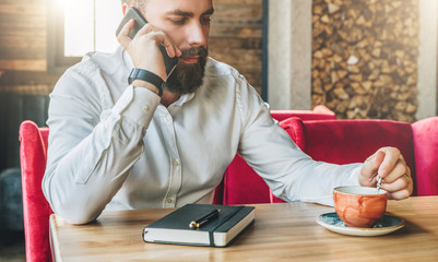 Young serious bearded businessman in white shirt is sitting in cafe at table and talking on his cell phone. On table is notebook and cup of tea. Online education, marketing. Lifestyle, startup.