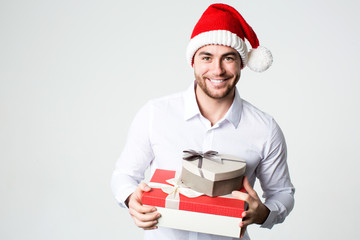 Smiling man in Santa hat with gift boxes.