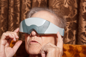 senior woman give eye massage with eye massage tool very similar with virtual reality device.