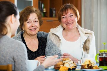 Senior women talking with girl while tea drinking