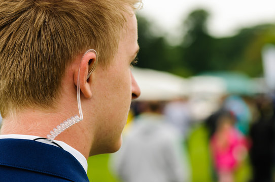 A young security guard wearing a coiled earpiece to listen to his two-way radio