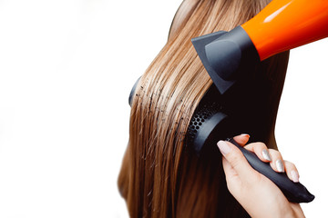 master in a hairdresser dries her hair to a girl with a hairdryer and makes a styling, isolated background