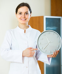 Female family doctor with big clock.