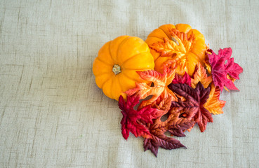 2 small pumpkins covered with colorful autumn leaves on a tan cloth background