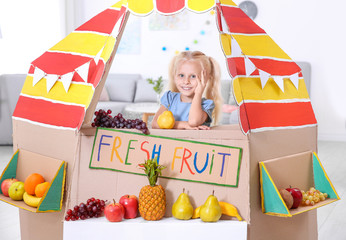 Cute little girl selling fruits at counter indoors