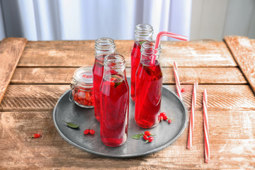Bottles with goji juice on tray