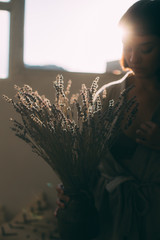 Soft focus shot of woman holding lavender bouquet with dry flowers, in nice evening light, florist of decorator designer