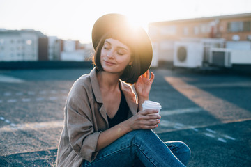 Portrait of beautiful young woman, in cute and adorable outfit, linen coat and fedora stylish fashion hat, drinks coffee from to go take away cup in amazing sunset light flares