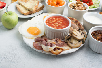 English breakfast made with fried eggs, sausages, bacon and mushrooms with selection of fruits and vegetables, breads and juice on the grey white table, copy space for text, selective focus