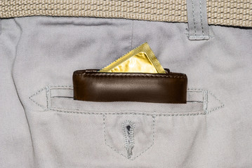 wallet in a pocket of white jeans with a gold condom