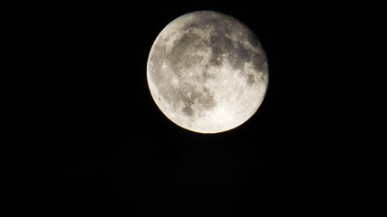 Bright Full-Moon phase with many craters and a little bit of water vapor in a dark sky.