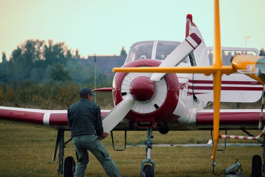 Man is trying to start engine by rotating propeller