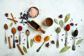 Various colorful indian spices and herbs in silver spoons on white background