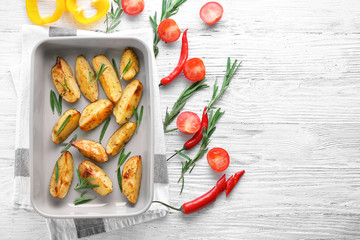 Composition with delicious rosemary potatoes in baking dish on table