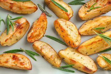 Delicious baked potatoes with rosemary on light background, closeup