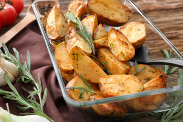 Delicious baked potatoes with rosemary in baking dish on table