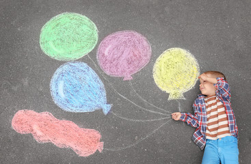 Little boy lying near chalk drawing of air balloons on asphalt