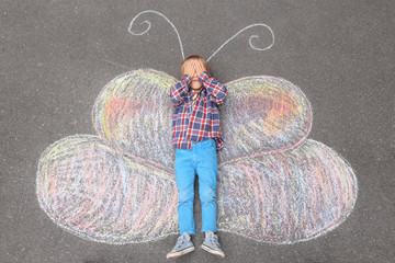 Little boy lying on chalk drawing of butterfly outdoors