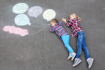 Little boy and girl lying near chalk drawing of air balloons on asphalt