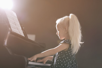 Little girl playing piano at concert indoors