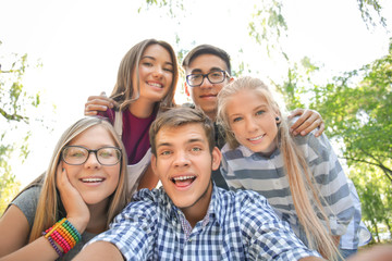 Happy teenagers taking selfie outdoors