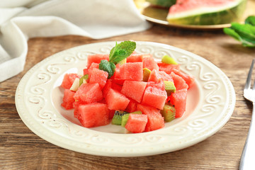 Plate of fresh salad with watermelon on table