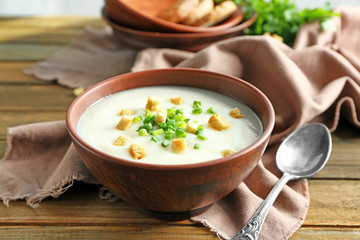 Bowl with potato cream soup on table