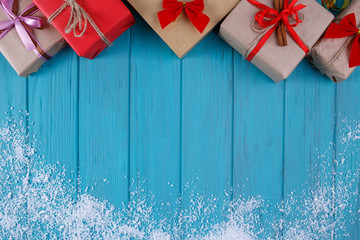Christmas, New year holidays background. Gift boxes and snowflakes on bright wooden board with copy space for your text design