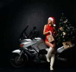 Portrait of sexy blonde woman in Christmas Santa costume sitting ride motorcycle