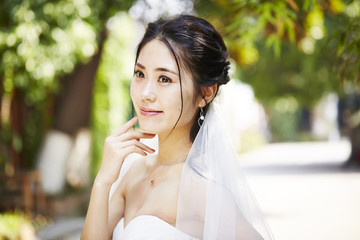 outdoor portrait of happy asian bride