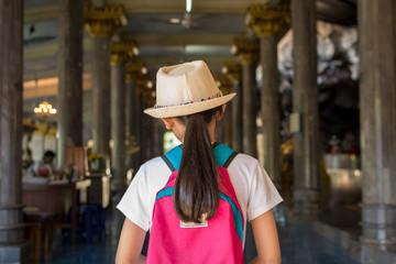 Girl with backpack entering to buddhist temple at Wat Tham Seua, Thailand.