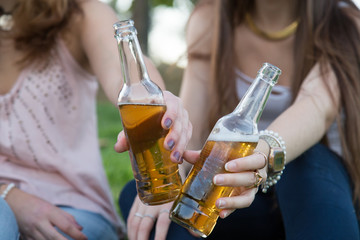Two young laughing women posing on lawn in park and toasting with beer bottles having fun.