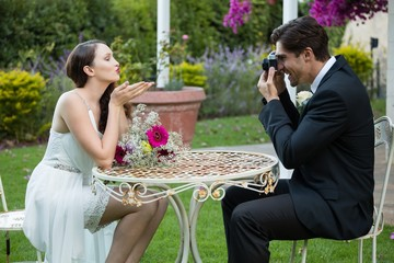 Bridegroom photographing bride blowing kiss while sitting at