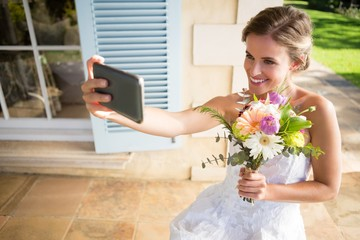 Happy bride holding bouquet taking selfie with mobile phone