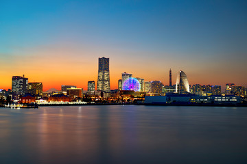 The city skyline at sunset of Yokohama, Japan with all the buildings illuminated and Cosmo Clock 21 spinning