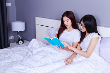 two woman reading a book on bed in bedroom
