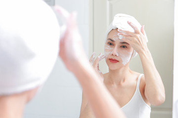 Woman happy cleanses the skin in the bathroom.