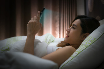 Woman with using modern devices on screen before sleep.