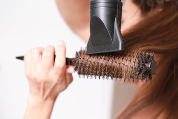 Drying Brown hair with hair dryer and round brush.