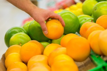Closeup of a Hand Picking a Fruit in a Supermarket