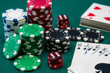 Poker chips, dice and Royal Flush card combination on green table