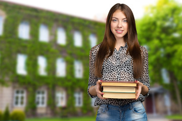 Smiling business woman holding stack of books