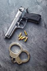 Pistol bullets, handgun and handcuffs.