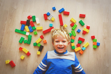 happy little boy love playing with plastic blocks