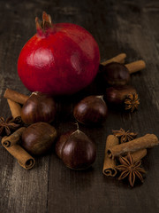 Chestnut and Pomegranate  together cinnamon and star anise on a wooden background