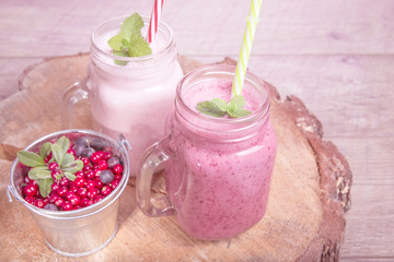 Assorted fruit or berry milk shakes in mason jar on wooden desk and table. Smoothie healthy eating concept