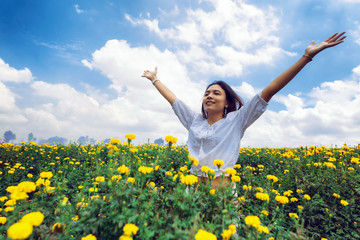 Happy woman enjoying in nature on sunflower garden on top of mountain cliff with sunrise; Beauty Girl Outdoor; Freedom concept.