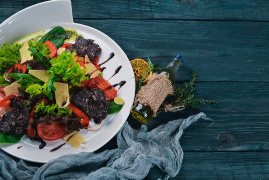 Beef Salad and Fresh Vegetables. On a wooden surface. Top view. Free space for your text.
