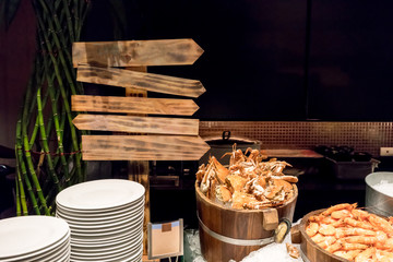 Steamed crabs and prawns on ice in wooden buckets with directional sign for menu