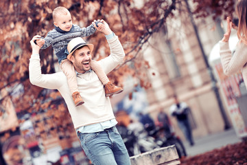 Happy father and his little son having fun in autumn park
